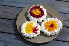 Meringue tartlets filled with fruitsserved on plate on wooden table Stock Photography