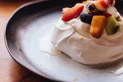 Meringue topping with fresh fruits including strawberry, mango, kiwi, blueberry and common fig served with sour fruit sauce Royalty Free Stock Images