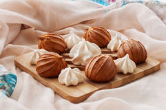 Meringues and eclairs. On a wooden board Stock Photo