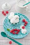 Meringues with fresh raspberries. On a pink plate Stock Photo