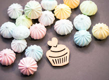 Meringues in pastel colors with wooden figure of cupcake on grey background. Royalty Free Stock Photography