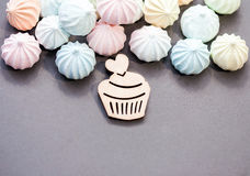 Meringues in pastel colors with wooden figure of cupcake on grey background. Royalty Free Stock Images