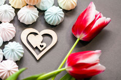 Meringues in pastel colors with wooden figure of heart and three red tulips on grey background. Royalty Free Stock Image