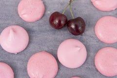 Meringues roses avec des cerises sur le gris Photo libre de droits