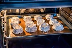 Meringues savoureuses blanches faisant cuire au four en four Images libres de droits