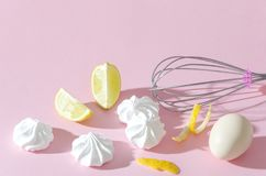 Meringues,slices of lime, egg and whisk on the pink background. Stylish preparing dessert royalty free stock photos