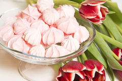 Meringues and tulips Stock Images