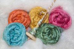 Merino and silk fibers. And a handspindle, colorfull fleeces for spinning and handycrafts stock photography