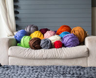 Merino wool balls in multicolour lying on white sofa with merino. Wool grey blanket on a floor stock image
