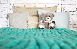 Merino wool blanket on bed with pillows in pastel colors and Ted Stock Photography