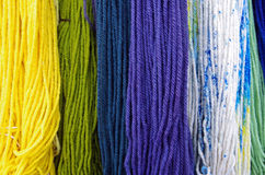 Merino wool colorful dyed textile. Long hanging strands stock photography
