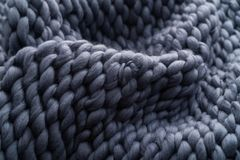 Merino wool handmade knitted large blanket, super chunky yarn, trendy concept. Close-up of knitted blanket, merino wool background royalty free stock photo