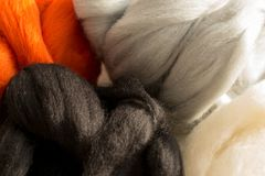 Merino wool, white, black, red and gray colors, for felting, close up. Colorful merino wool, white, black, red and gray colors, for felting, close up Royalty Free Stock Photo