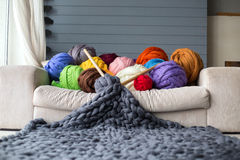 Merinowollebälle im Mehrfarbenlügen auf weißem Sofa mit Merino Lizenzfreie Stockfotos