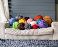 Merinowollebälle im Mehrfarbenlügen auf weißem Sofa mit Merino Stockbild