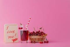 Merises dans un jus de panier et en verre sur le fond rose Photographie stock