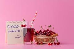 Merises dans un panier et un verre de jus sur le backgroun rose Photo stock