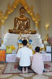 Merit Makers at a Buddhist Temple. Visitors make merit in the hall of Wat Traimit temple, which houses the world's largest solid gold Buddha statue on March 2 Royalty Free Stock Photo