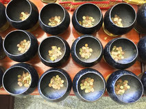 Merit. Top view the little gold coins put in row of black alms-bowls on wooden table. The merits and donation for happiness ans good luck at the buddist temple Royalty Free Stock Photos