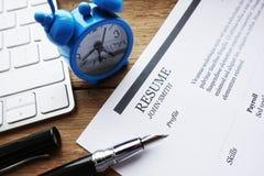 Meritförteckning eller program - vitae på ett träskrivbord nära ett datortangentbord arkivbilder