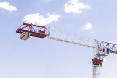 Meriton crane fixed under blue sky with white clouds. Made in steel material to construct buildings and lift heavy items Royalty Free Stock Images