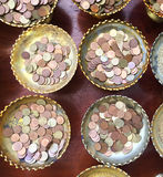 Merits and donation. Top view the little coins put in row of tray with pedestal. The merits and donation for happiness ans good luck at the buddist temple in Royalty Free Stock Photo