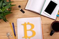Merkt bitcoins im Notizblock auf dem Schreibtisch eines Geschäftsmannes Stockbilder