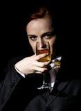 Merkwürdige Frau in einer Mann ` s Klage trinkt Champagner auf einem dunklen Hintergrund lizenzfreie stockfotografie
