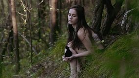 Merkwürdige und starke tragende Pelzspitze der jungen Frau sitzt auf dem Waldhügel und -c$denken stock footage