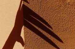 Merkwürdiger Handschatten auf einer orange Steinwand Schwarzer Schatten, weibliche Hand lizenzfreie stockfotografie