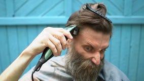Merkwürdiger Hippie-Mann mit dem großen grauhaarigen Bart, der versucht zu schneiden, Haar mit Elektrorasiererscherer zu besitzen stock footage