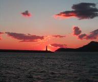 Merkwürdiger Sonnenuntergang an der Küste Stockfotos