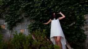 Merkwürdiger Traum Mädchen über dem Abgrund vor dem hintergrund einer hohen efeubewachsenen Wand stock video