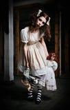 Merkwürdiges furchtsames Mädchen mit Puppen in den Händen lizenzfreie stockfotos