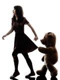 Merkwürdige junge Frau und schändliches Teddybärschattenbild Stockfotografie