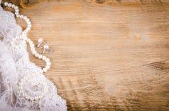 Merletti, collana della perla, orecchini su fondo di legno, rustico Immagini Stock