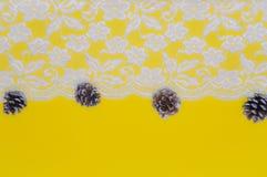 Merletti i confini e le ghiande contro un fondo giallo come concetto delle stagioni cambianti, Natale Immagini Stock