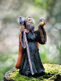 Merlin In The Forest. Merlin figurine in a woodland setting with the low winter light catching his globe Royalty Free Stock Photos
