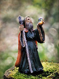 Merlin In The Forest - Textures. Merlin figurine in a woodland setting with the low winter light catching his globe. Textures added Stock Image