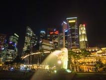 Merlion雕象喷泉和城市地平线在晚上在新加坡 免版税库存照片