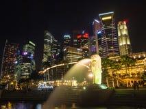 Merlion雕象喷泉和城市地平线在晚上在新加坡 免版税库存图片