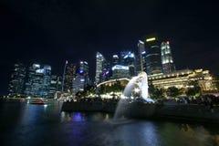 Merlion雕象喷泉在Merlion公园和新加坡城市地平线在晚上 免版税库存照片
