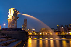 Merlion fountain in Singapore. Merlion fountain spouts water in front of the Singapore skyline in night. Merlion is an imaginary creature with the head of a lion Royalty Free Stock Photo