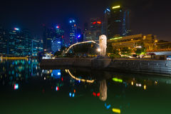 The Merlion fountain and Singapore skyline by night. Merlion is Stock Photos