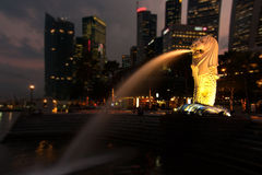 Merlion Park in Singapore with evening. Singapore.View on Merlion park and statue.Summer evening.Backlighted monument on yellow.in the background visible offiIe Royalty Free Stock Photography
