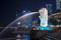 Merlion of Singapore by night, business buildings in the background Stock Photography