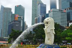 The Merlion statue in front of financial and business district of Singapore. Skyline of the financial district of Singapore taken at dusk. The buildings shows Stock Image