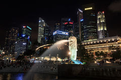 The Merlion statue in front of Singapore skyline at night. Singapore, Singapore - May 18, 2015: The Merlion statue and Singapore skyline at night. The Merlion is Stock Image