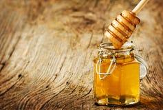 Merlo acquaiolo del miele sopra un barattolo su un vecchio legno d'annata fotografia stock libera da diritti