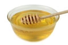 Merlo acquaiolo di legno e del miele in ciotola di vetro Immagini Stock Libere da Diritti